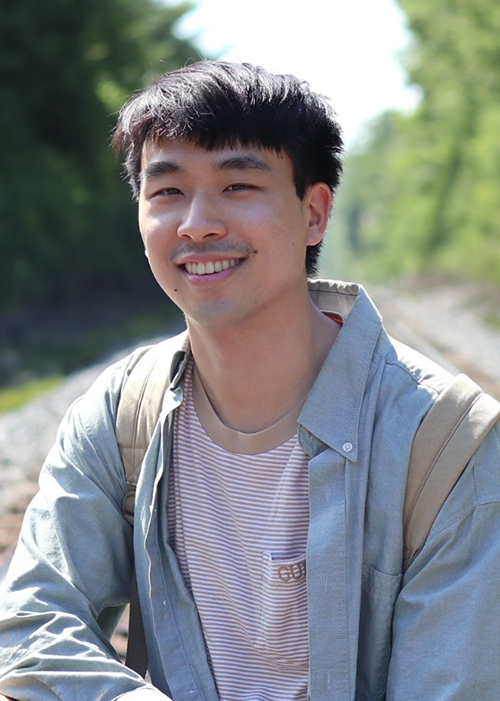 Tim Chan posing for a picture outdoors