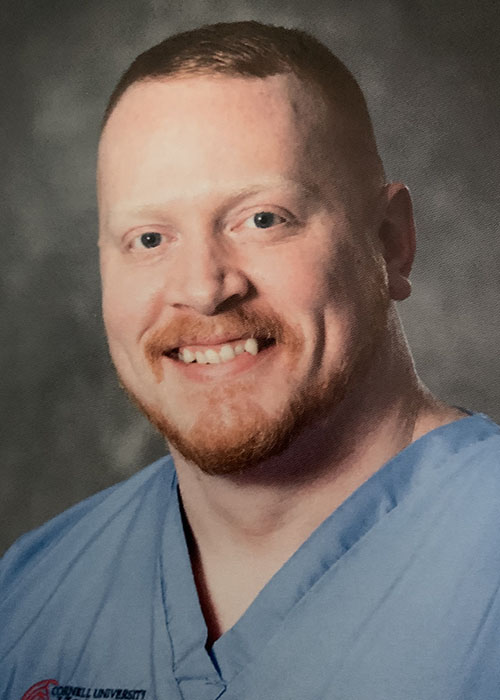 Bryan Clifford posing for a headshot in blue scrubs