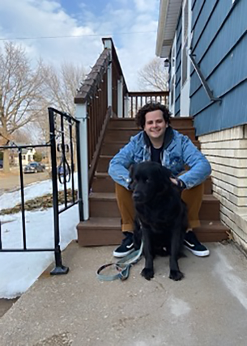 Jonathan Elbaz sitting on steps posing for picture with his black labrador retriever