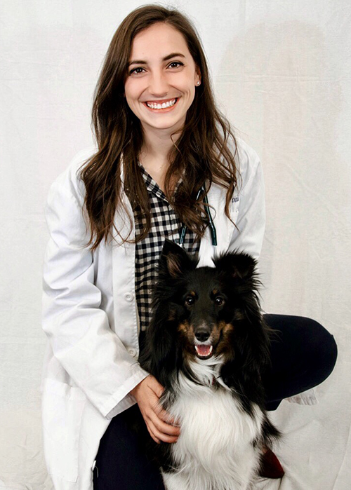 Savannah Giannasi posing for a picture in her medical white coat with her shetland sheepdog