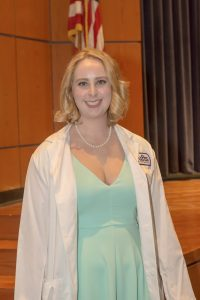 Katelyn McFadden in her white coat posing for picture after 2018 White Coat Ceremony